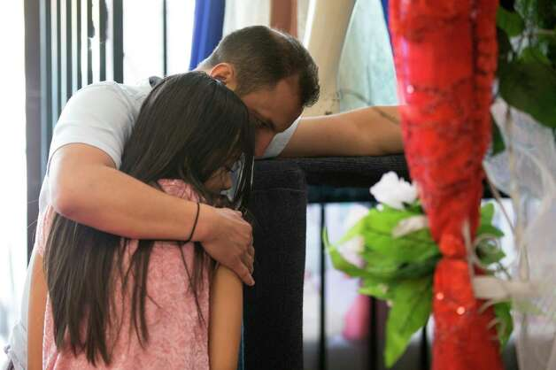 Crispin Andrade hugs his daughter, Guadalupe, inside the Lety's Quinceañeras store Saturday, Oct. 7, 2017, in Houston. The family postponed Guadalupe's quinceañera due to her father traveling back to Mexico to apply for U.S. residency, not knowing whether he would be allowed back into the country. Photo: Godofredo A. Vasquez, Houston Chronicle / Godofredo A. Vasquez