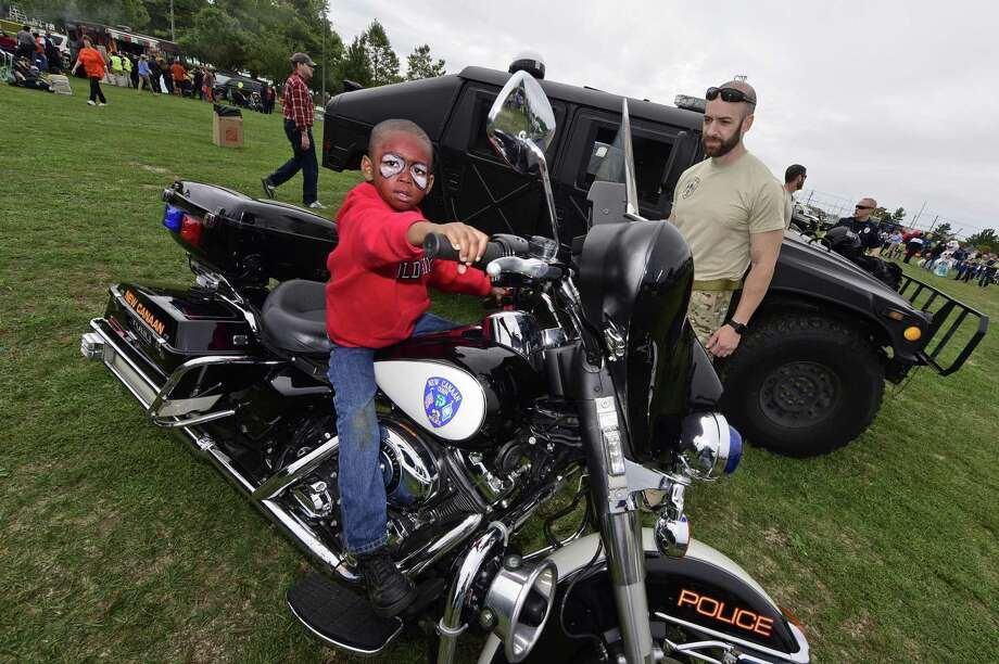 Caden Webb, then 4, climbs aboard a New Canaan Police Department motorcycle under the watchful eye of Sgt. Joe Farenga during the Human Services Council's annual KidzFest in October 2016 at Taylor Farm Park in Norwalk. Photo: Erik Trautmann / Hearst Connecticut Media / Norwalk Hour