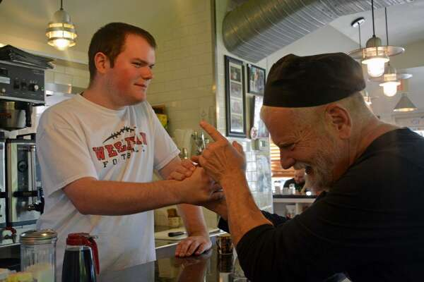 Luke Whalen, 21, of Durham, left, jokes with O'Rourke's Diner owner Brian O'Rourke Tuesday afternoon in Middletown during a break from sweeping the floors. Whalen, who has high-functioning autism and has been working at the restaurant since August, is a perfect fit for the job, O'Rourke said.