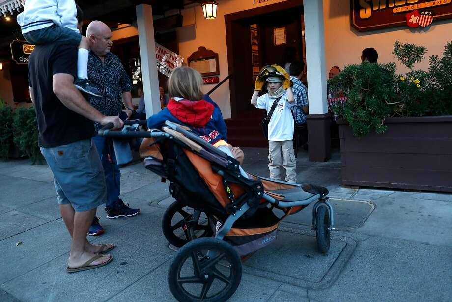 After returning from a week-long vacation in Canada, Cameron Menefee, 6, wears firefighter gear to show support for firefighters at the Swiss Hotel in Sonoma. The hotel's owner, Hank Marioni, lost his home of 35 years to the fire. Photo: Scott Strazzante, The Chronicle