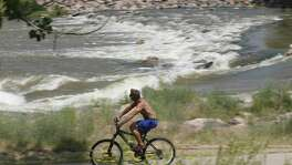 In this Tuesday, June 23, 2015, file photo, a bicyclist navigates a trail as the South Platte River flows in the background in Englewood, Colo., near Denver. In an effort to woo Amazon to build its second headquarters in the metro Denver area, the Metro Denver Economic Development Corp. is compiling a formal bid that highlights Colorados 45,000 miles of hiking, biking and all-purpose trails.