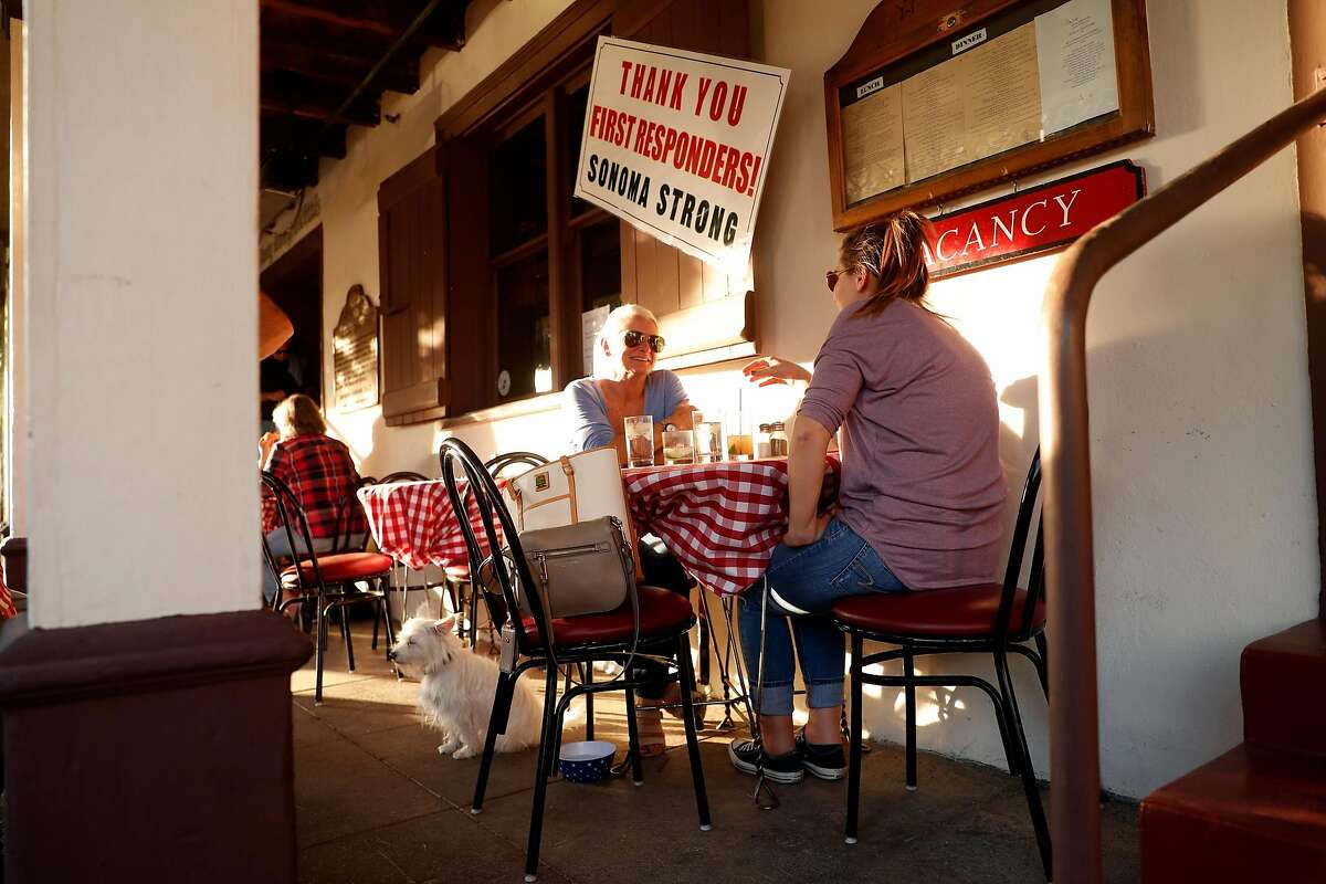 Charys Sayre, her dog, Mikey, and Jenna Glazier enjoy dinner at the Swiss Hotel on Spain Street in Sonoma. The hotel, which has been in the same family for 95 years, had lost many paying customers, but people were starting to come back for dinner.