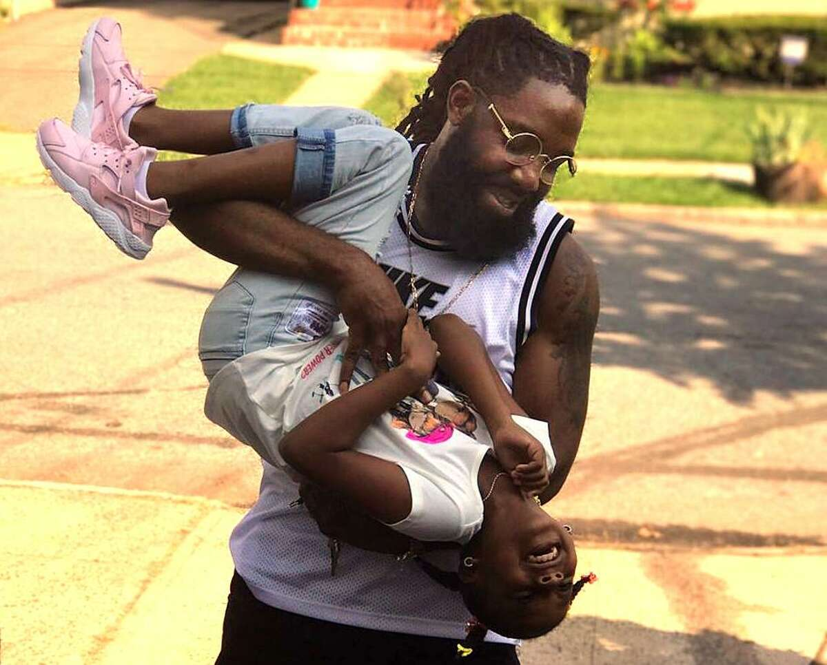 Deon Rodney, 31, who was murdered in Bridgeport at the barbershop where he worked, plays with his daughter in this undated photo taken by a family member. His widow's co-workers are organizing a fundraiser to pay for his funeral and other costs.