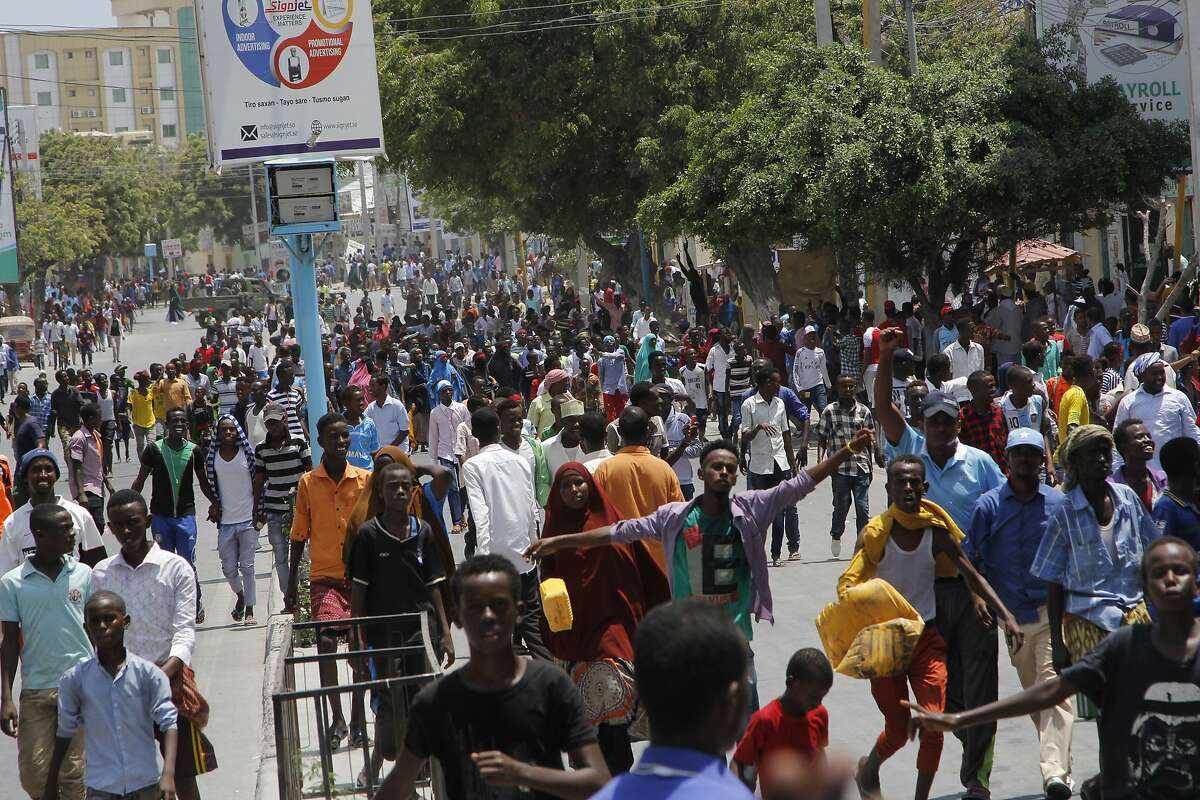 Protesters march near the scene of Saturday's massive truck bomb attack in Mogadishu, Somalia, Wednesday, Oct. 18, 2017. Thousands of people took to the streets of Somalia's capital Wednesday in a show of defiance after the country's deadliest attack, as two people were arrested in connection with Saturday's massive truck bombing that killed more than 300. (AP Photo/Farah Abdi Warsameh)