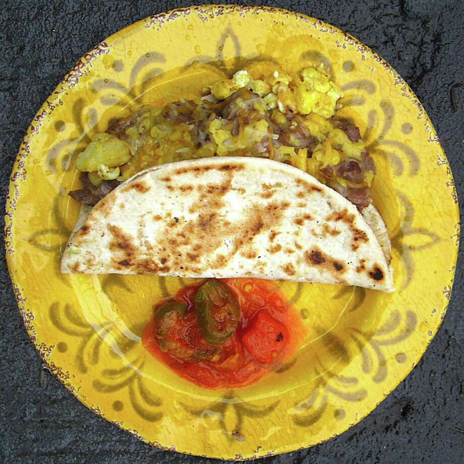 Taco of the Week: A taco called simply Moe starts as a simple potato and egg taco on a toasted handmade flour tortilla, but then it goes turbo with carne guisada gravy and cheese at Georgia's Mexican Restaurant. Photo: Mike Sutter /San Antonio Express-News