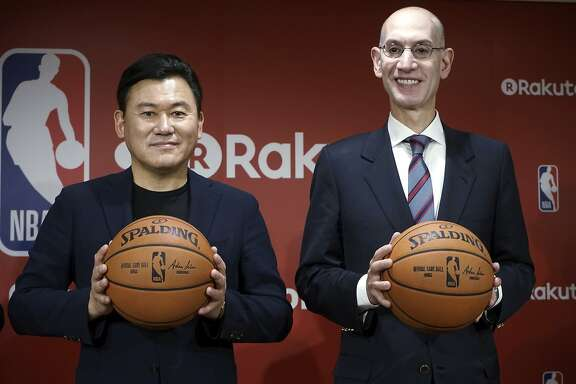 Adam Silver, right, the commissioner of the National Basketball Association (NBA) and Hiroshi Mikitani, left, chairman and CEO of Rakuten, Inc. pose for photographers during the joint press conference in Tokyo Tuesday, Oct. 10, 2017. Japanese online retailer Rakuten will be NBA's exclusive distribution partner in Japan for live NBA games and a global marketing partner of the NBA. (AP Photo/Eugene Hoshiko)