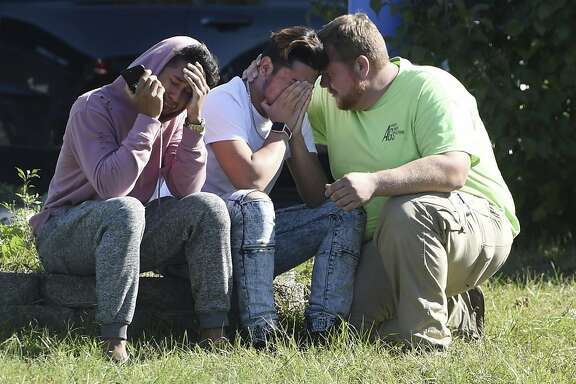 Workers from the Advanced Granite Solutions company console each other as police and Emergency Medical Services respond to a shooting at a business park in the Edgewood area of Harford County, Md., Wednesday, Oct. 18, 2017.  A gunman opened fire at the office park killing several co-workers and wounded others, authorities said.  (Matt Button/The Baltimore Sun via AP)
