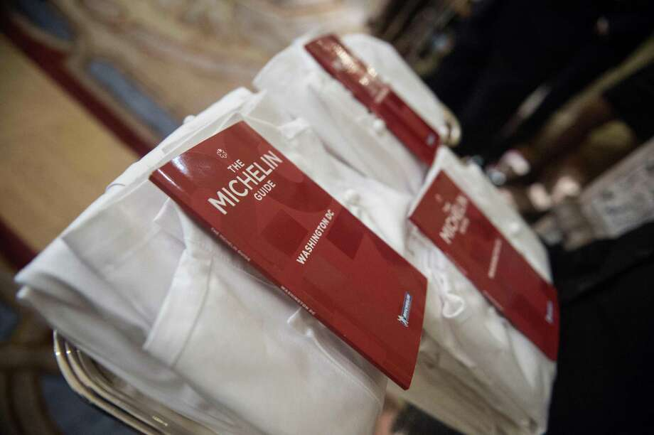 "The first Michelin Red Guide for Washington is seen at the residence of the French ambassador during its launch in Washington, DC, on October 13, 2016. In looking at the 2018 guide, it would be tough to qualify any of the Washington D.C. eats in a Bib Gourmand, which highlights ""cheap eats."" / AFP PHOTO / NICHOLAS KAMMNICHOLAS KAMM/AFP/Getty Images Photo: NICHOLAS KAMM / AFP or licensors"