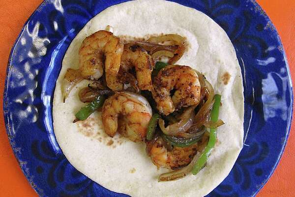 Shrimp taco with grilled onions and peppers on a handmade flour tortilla from Brenda's Mexican Restaurant.