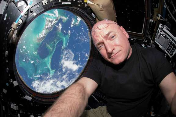 In this July 12, 2015 photo, Astronaut Scott Kelly takes a photo of himself inside the Cupola, a special module of the International Space Station which provides a 360-degree viewing of the Earth and the station.