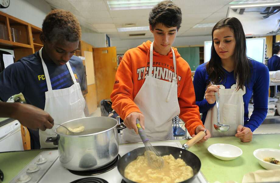 From left; Sophomores Derick Celestin, Nick Gloria, and Amanda Zdru cook potato gnocci in a chicken veloute in their Intro to Culinary Arts class at Bunnell High School in Stratford, Conn. on Wednesday, October 18, 2017. With their teacher, Brian Neumeyer, the students will be cooking once monthly meals for Stratford veterans. Photo: Brian A. Pounds / Hearst Connecticut Media / Connecticut Post