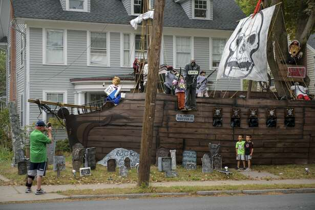 A resident in the neighborhood, Roger Poudrier, takes a photo of his twin sons Joshua, left, and Jayden, right, next to the display. An elaborate Halloween display is put up in front of Matt Warshauer's home every year in West Hartford, Conn., Oct. 11, 2017. This year the theme is political with models of Hillary Clinton, Donald Trump, James Comey, and more. (Monica Jorge/The Courant via AP)