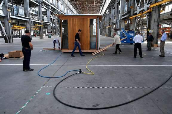 Workers conduct a test of their air casters used to move the modular structures around using hydraulic air, inside the huge building at Factory_OS where they are ramping up to build well-designed, tech-ready multifamily homes 40% faster and 20% less expensive than conventional housing on the grounds of the famous Mare Island Shipyard in Vallejo, Ca., as seen on Mon. September 11, 2017.