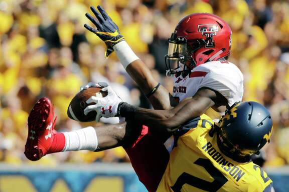 Texas Tech wide receiver T.J. Vasher, top, catches a pass for a touchdown while being defended by West Virginia safety Kenny Robinson (2) during the first half of an NCAA college football game, Saturday, Oct. 14, 2017, in Morgantown, W.Va. (AP Photo/Raymond Thompson)