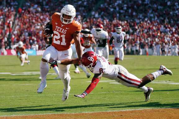 Texas running back Kyle Porter (21) takes a touchdown pass and gets past Oklahoma safety Kahlil Haughton (8) to score during the first half of an NCAA college football game, Saturday, Oct. 14, 2017, in Dallas, Texas. (AP Photo/Ron Jenkins)