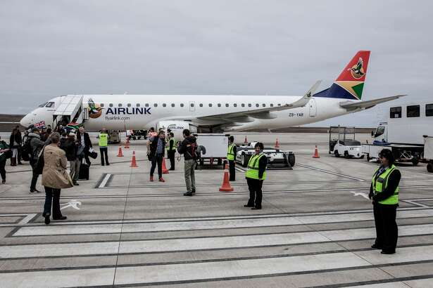 Travellers and passengers get off the first inaugural commercial plane from Johannesburg after landing at the newly built Saint Helena Airport in the volcanic tropical island of Saint Helena, in the South Atlantic Ocean and part of the British Overseas Territory on Oct. 14, 2017.  After five years of construction, controversy and embarrassing delays due to high winds, an airport built at a cost of £285 million (318 million euros) will welcome its first routine flight from Johannesburg.