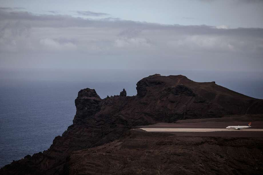A picture taken on Oct. 14, 2017 shows the first commercial airplane from Johannesburg before its take off at the newly built Saint Helena Airport in the tropical island of Saint Helena, in the South Atlantic Ocean and part of the British Overseas Territory. After five years of construction, controversy and embarrassing delays due to high winds, an airport built at a cost of £285 million (318 million euros) will welcome its first routine flight from Johannesburg. Photo: GIANLUIGI GUERCIA/AFP/Getty Images