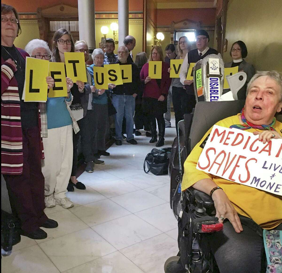 Activists, urging Connecticut state legislative leaders not to cut Medicaid spending, wait outside the room where a new two-year, bipartisan budget agreement was being negotiated, Wednesday, Oct. 18, 2017, at the Capitol in Hartford, Conn.