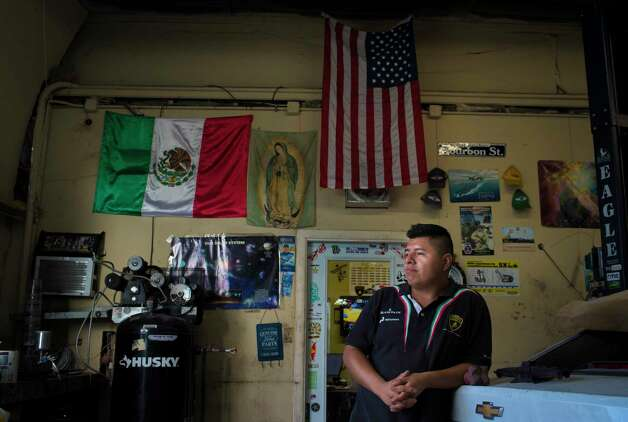 Freddy Avan, 28, stands on front of the Mexican flag and the United States flag at his automobile repair shop, Wednesday, June 28, 2017 in Katy. Avan who is an immigrant in the country illegally, has been the owner of the shop in Katy for the past four years and employing seven mechanics. Photo: Marie D. De Jesus, Houston Chronicle / © 2017 Houston Chronicle
