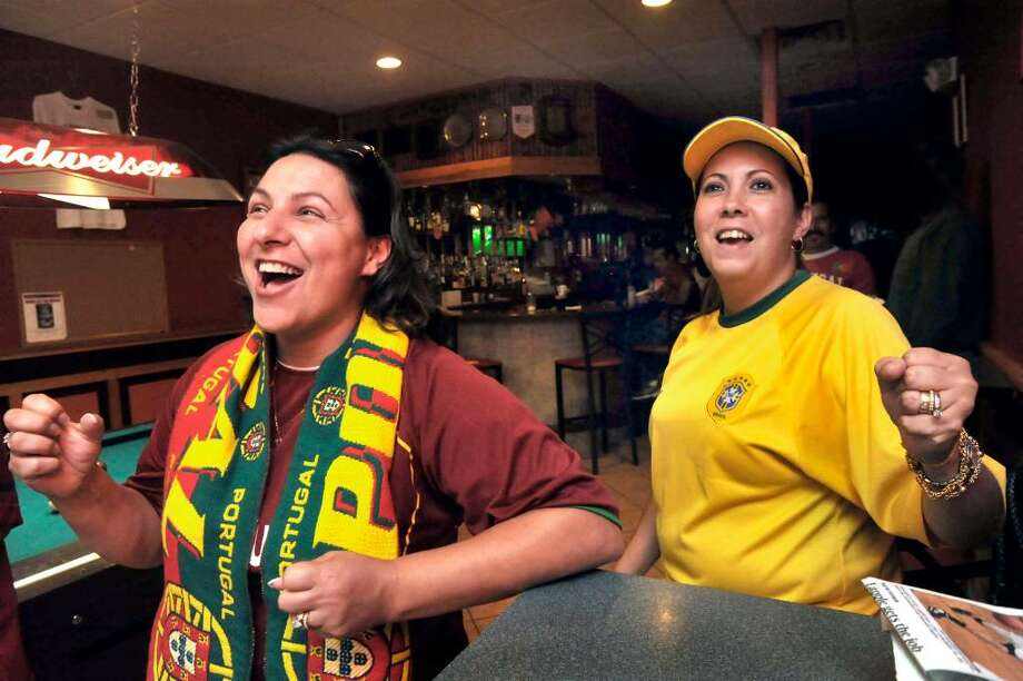 Carla Carreiro, left, roots for Portugal while Graziane Cordeiro, roots for Brazil while watching World Cup Soccer at Casa Do Benfica Soccer & Social Club in Danbury on Friday, June 25, 2010. Photo: Michael Duffy / The News-Times