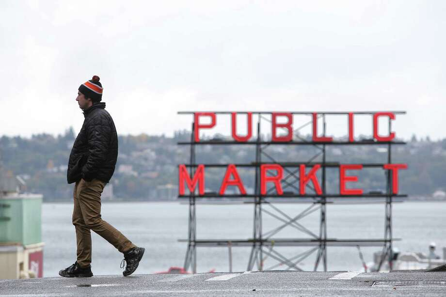 Wearing a hat and jacket, a man walks past Pike Place Market as rain and wind storms roll in to Seattle, Wednesday afternoon, Oct. 18, 2017. Photo: GENNA MARTIN, SEATTLEPI / SEATTLEPI.COM
