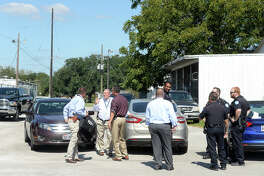 Beaumont police and detectives gather and talk behind the Best Years Senior Center following a shooting and car theft Wednesday. An elderly woman was taken for treatment to an area hospital after being shot in the head behind the facility.  Photo taken Wednesday, October 18, 2017 Kim Brent/The Enterprise