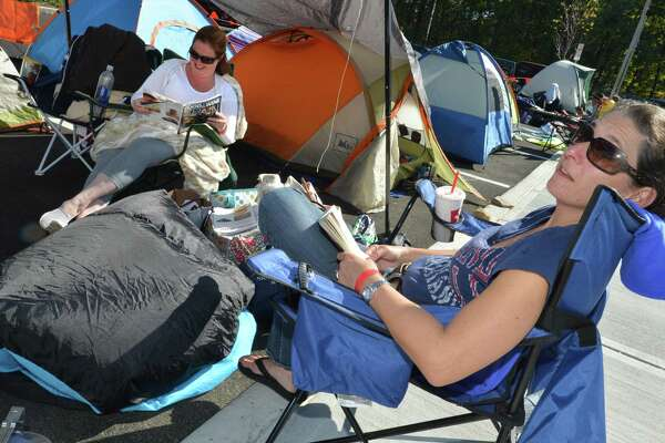 Trumbull's Shannon Oddis and Norwalk's Traci Tarnok read some magazines to pass the time in the parking lot while camping out to win 52 combo meal vouchers for the first 100 people at the new Chick-fil-A in Norwalk. About two dozen were camped out on Wednesday October 18, 2017 until Thursday morning's grand opening of the new Chick-fil-A  on Connecticut Ave. in Norwalk Conn.
