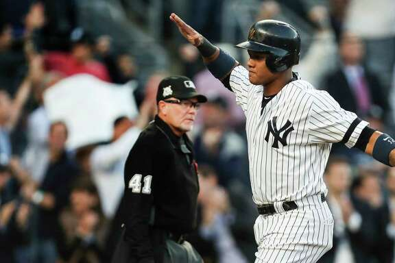 New York Yankees second baseman Starlin Castro reaches out to high five Todd Frazier (29) after scoring on a Greg Bird single off Houston Astros starting pitcher Dallas Keuchel during the second inning of Game 5 of the ALCS at Yankee Stadium on Wednesday, Oct. 18, 2017, in New York.