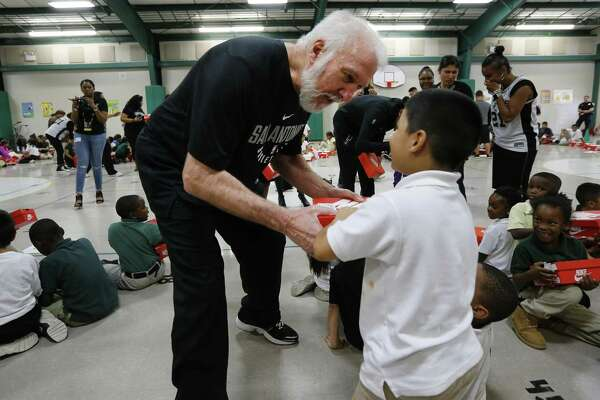 """Spurs Coach Gregg Popovich (pictured) and Spurs' guard Dejounte Murray make an appearance at SAISD's Gates Elementary to deliver shoes to students on Wednesday, Oct. 4, 2017. The Spurs in conjunction with the non-profit organization, Shoes That Fit, and Coach Popovich gave new shoes to every student enrolled at Gates Elementary. Popovich, Murray, The Coyote and Spurs Silver Dancers joined over 200 elementary in the gym. Boxes of new shoes were handed out to each students as cheers of """"Go Spurs Go"""" echoed off the walls. Each student was measured for a new pair of sneakers. Shoes That Fit then hand-selected each pair of shoes and compiled the order for Wednesday's delivery. Located in the Eastside Promise Neighborhood, over 95 percent of Gates Elementary students are economically disadvantaged. Shoes That Fit Shoes That Fit is a national, nonprofit 501(c)3 organization based in Claremont, Calif., and is the nation's largest nonprofit provider of new athletic shoes to children in need. Shoes That Fit tackles one of the most visible signs of poverty in America by giving children in need new athletic shoes to attend school with dignity and joy, prepared to leave, play and thrive. The program is designed to improve a child's self-esteem. In 2016 Shoes That Fit programs delivered new athletic shoes to over 103,000 children in over 2,100 schools throughout 46 states, Washington D.C. and Puerto Rico. (Kin Man Hui/San Antonio Express-News)"""