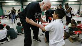 "Spurs Coach Gregg Popovich (pictured) and Spurs' guard Dejounte Murray make an appearance at SAISD's Gates Elementary to deliver shoes to students on Wednesday, Oct. 4, 2017. The Spurs in conjunction with the non-profit organization, Shoes That Fit, and Coach Popovich gave new shoes to every student enrolled at Gates Elementary. Popovich, Murray, The Coyote and Spurs Silver Dancers joined over 200 elementary in the gym. Boxes of new shoes were handed out to each students as cheers of ""Go Spurs Go"" echoed off the walls. Each student was measured for a new pair of sneakers. Shoes That Fit then hand-selected each pair of shoes and compiled the order for Wednesday's delivery. Located in the Eastside Promise Neighborhood, over 95 percent of Gates Elementary students are economically disadvantaged. Shoes That Fit Shoes That Fit is a national, nonprofit 501(c)3 organization based in Claremont, Calif., and is the nation's largest nonprofit provider of new athletic shoes to children in need. Shoes That Fit tackles one of the most visible signs of poverty in America by giving children in need new athletic shoes to attend school with dignity and joy, prepared to leave, play and thrive. The program is designed to improve a child's self-esteem. In 2016 Shoes That Fit programs delivered new athletic shoes to over 103,000 children in over 2,100 schools throughout 46 states, Washington D.C. and Puerto Rico. (Kin Man Hui/San Antonio Express-News)"
