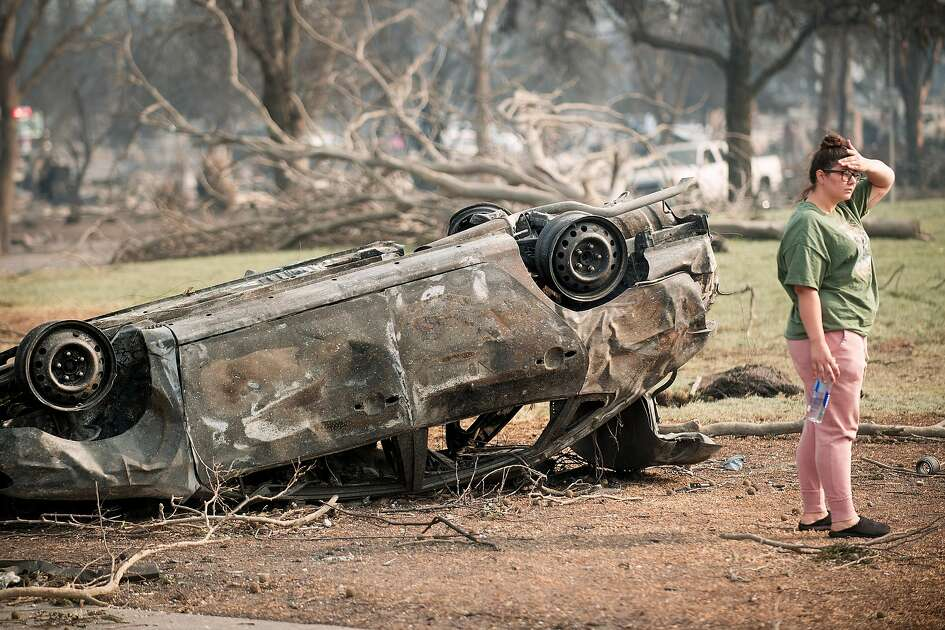 Standing next to a flipped car, Shannon Hoekstra surveys damage in the Coffey Park neighborhood of Santa Rosa, Calif., following the Tubbs fire on Tuesday, Oct. 10, 2017.