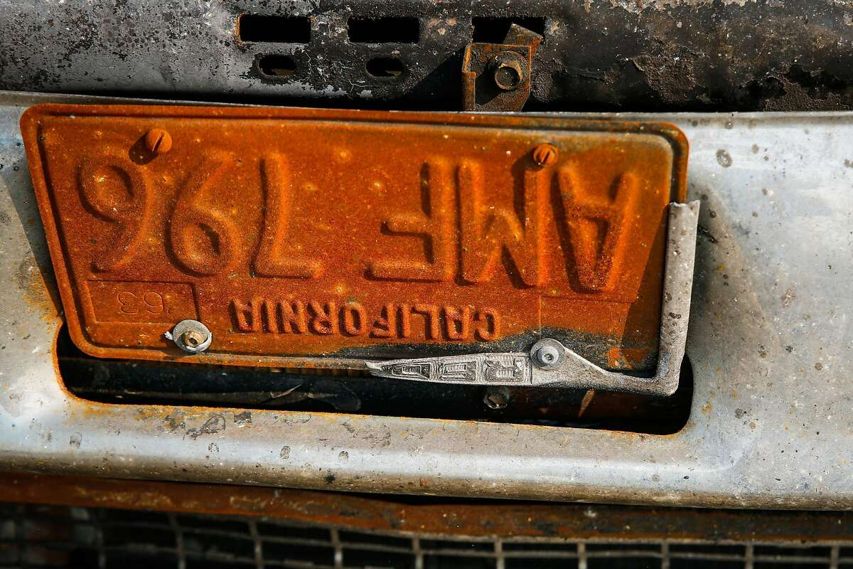 The license plate of a flipped car on Dogwood Drive in the Coffey Park neighborhood in Santa Rosa, Calif., on Wednesday, Oct. 18, 2017. A flipped car sits next to him in front of the residence. The cars were flipped in the Tubbs fire.