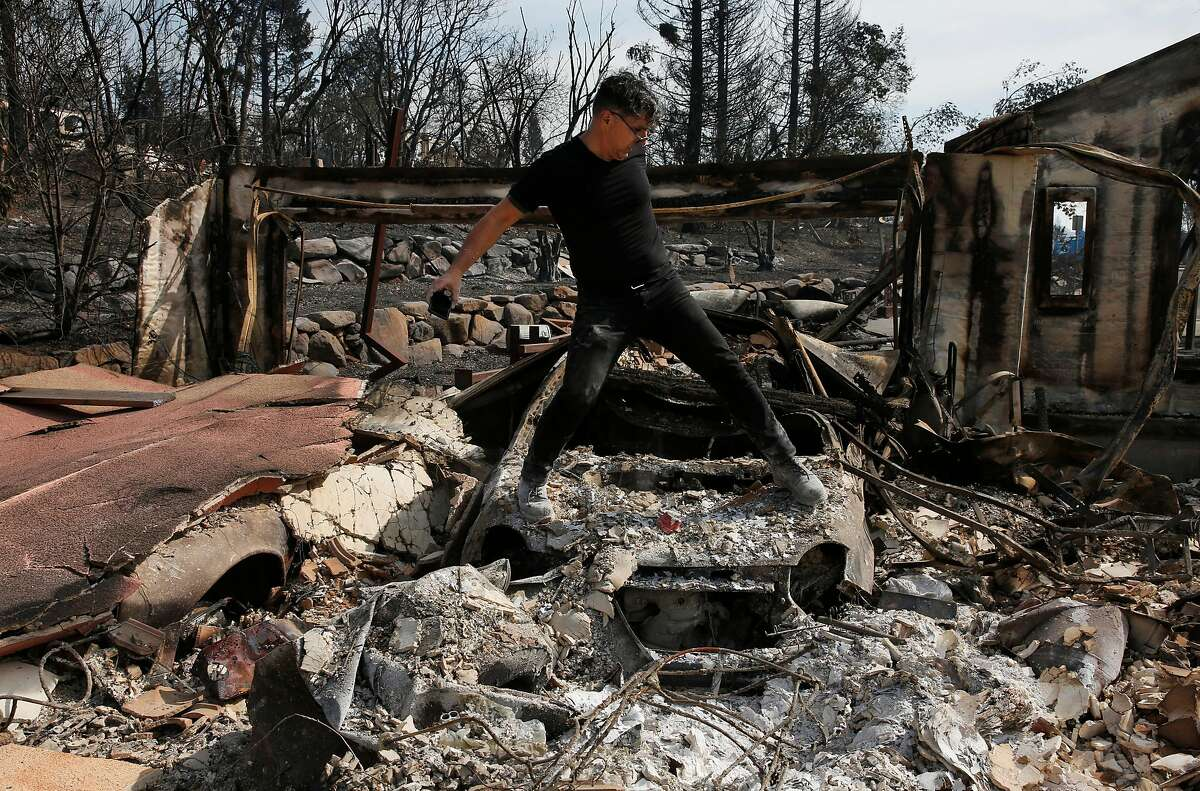 Boback Emad climbs across one of his destroyed cars to take photographs for his insurance company while surveying the destruction of his home for the first time in the Fountaingrove neighborhood Oct. 17, 2017 in Santa Rosa, Calif. Emad lost his home along with a career's worth of his artwork, which he had just moved back to his house as he was preparing to move it to a different facility. Emad was also an art collector and he lost several valuable pieces.