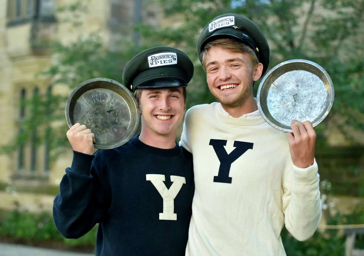 """New Haven, Connecticut - Wednesday, October 18, 2017: Yale University students Hudson Walberg, left, and Alec Emser of the Yale Mens Ultimate Frisbee team on the Yale campus hold Frisbie's Pies pie plates Wednesday while sporting Frisbie's Pies hats used by deliverymen of the original Frisbie's Pies company of Bridgeport. The pie plates were the original """"flying discs""""."""