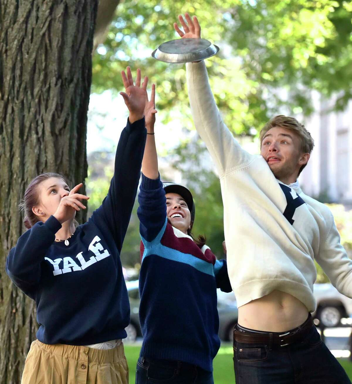 """New Haven, Connecticut - Wednesday, October 18, 2017: Yale University students Ella Schmidt, Isabelle Carson and Alec Emser of the Yale Men's and Women's Ultimate Frisbee team, left, to right, fight for control of a Frisbie's Pies pie plate Wednesday on the Yale University campus in New Haven. The pie plates were the original """"flying discs""""."""