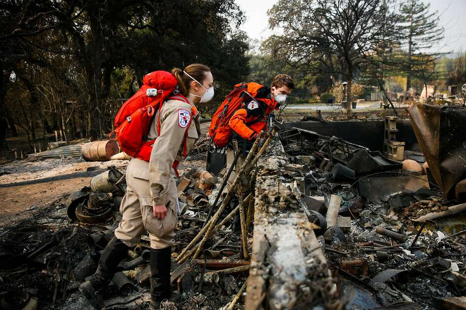 Allison Cote and Liam Ferguson (right) of the Contra Costa Search and Rescue survey a property off of Highway 12 in Glen Ellen, Calif., on Wednesday, Oct. 18, 2017.