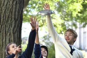 """From left, Yale University students Ella Schmidt, Isabelle Carson and Alec Emser of the Yale Men's and Women's Ultimate Frisbee team fight for control of a Frisbie's Pies pie plate Wednesday on the Yale University campus in New Haven. The pie plates were the original """"flying discs."""""""
