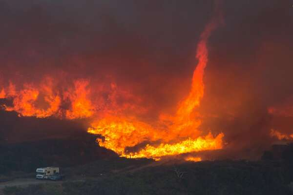 WRIGHTWOOD, CA - AUGUST 17: A fire tornado forms near cars parked on a country road at the Blue Cut Fire on August 17, 2016 near Wrightwood, California.. An unknown number of homes and businesses have burned and more than 80,000 people are under evacuation orders as the out-of-control wildfire spread beyond 30,000 acres and threatens to expand into the ski resort town of Wrightwood. (Photo by David McNew/Getty Images)