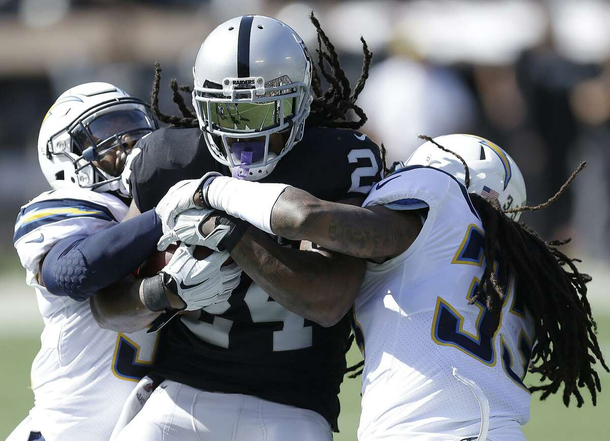 Marshawn Lynch struggles for yardage Sunday against the Chargers' Adrian Phillips (left) and Tre Boston. After a strong start in the game, Lynch had just five touches, and 14 yards, in the second half.