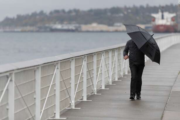 A walker tries to avoid sideways rain along the Seattle waterfront at the Sculpture Park Wednesday, Oct. 18, 2017. Wind gusts up to 45 mph and heavy rain were expected through Thursday morning across Western Washington in the first major storm of the fall.