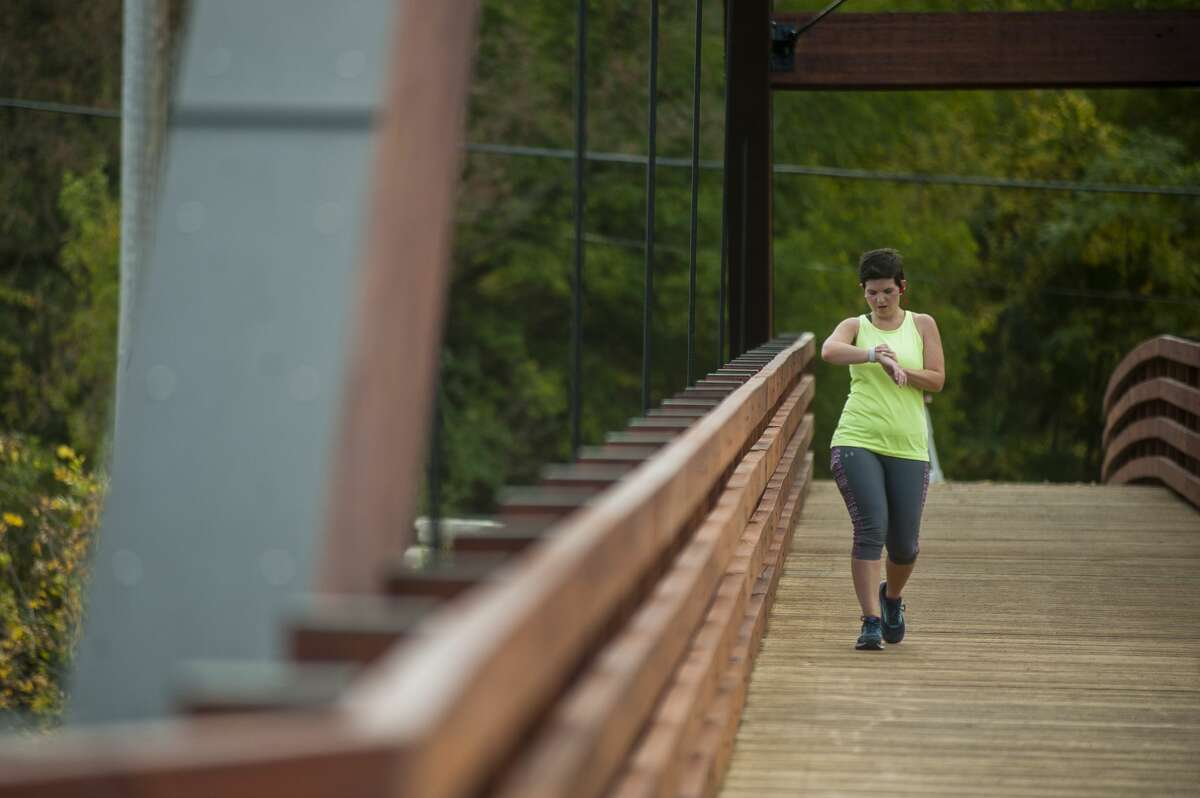 Sonya Lidke of Midland walks across the Tridge during her run on Tuesday, Oct. 10 while the Tridge was reopened for a sneak preview before renovations were finished. (Katy Kildee/kkildee@mdn.net)