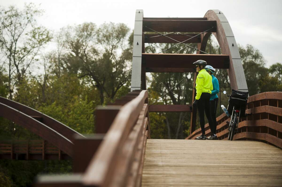 Two cyclists check out the view from the Tridge on Tuesday, Oct. 10 while the Tridge was reopened for a sneak preview before renovations were finished. (Katy Kildee/kkildee@mdn.net)