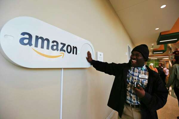Zavian Tate, a student at the University of Alabama at Birmingham, pushes a large Amazon Dash button. The Dash buttons are part of the city's campaign to lure Amazon's second headquarters.