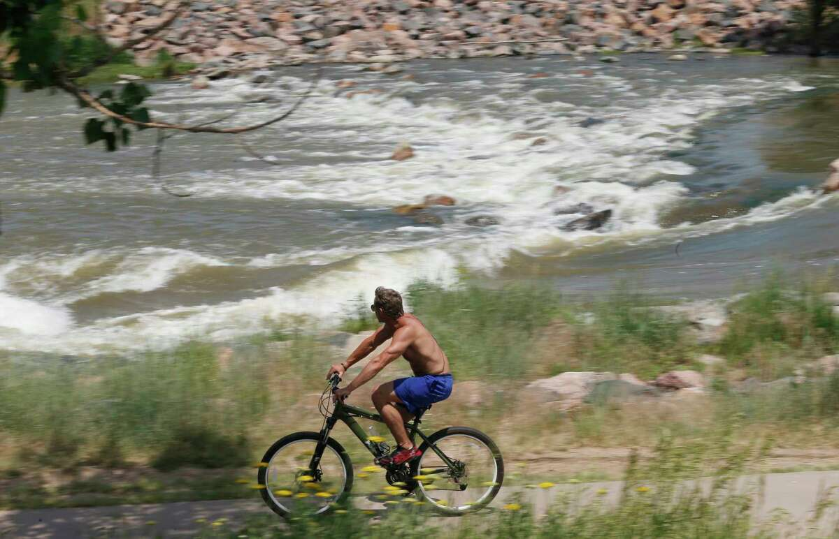 FILE - In this Tuesday, June 23, 2015, file photo, a bicyclist navigates a trail as the South Platte River flows in the background in Englewood, Colo., near Denver. In an effort to woo Amazon to build its second headquarters in the metro Denver area, the Metro Denver Economic Development Corp. is compiling a formal bid that highlights ColoradoÂ?'s 45,000 miles of hiking, biking and all-purpose trails. (AP Photo/David Zalubowski, File)