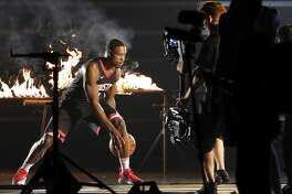 Houston Rockets' Demetrius Jackson dribbles amid flames as he takes part in a promotional video shoot during an NBA basketball media day, Monday, Sept. 25, 2017, in Houston. (AP Photo/Michael Wyke)