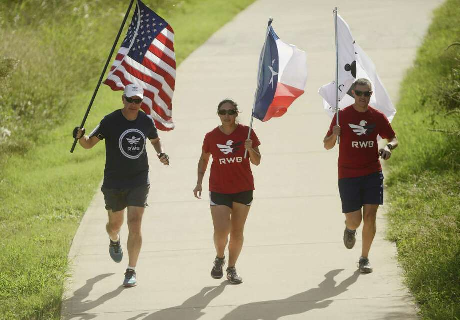 Adam Hartman (left), Aracely Renderos and Jeff Matney carry flags, including a U.S. flag that is being carried across the country, along the San Antonio River south of downtown on Wednesday. The theme of the fourth annual Old Glory Relay is unity and uniting people for a common purpose. Photo: Billy Calzada /San Antonio Express-News / San Antonio Express-News