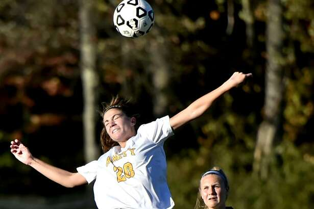 Woodbridge, Connecticut - Wednesday, October 18, 2017:  Kelsey Morgan of Amity H.S. heads the ball as Grace Wooten of Jonathan Law H.S of Milford  is in pursuit, right, during second half soccer action at Amity H.S.  Wednesday afternoon in Woodbridge. Final Score: Amity H.S. defeats Jonathan Law H.S. 1-0.