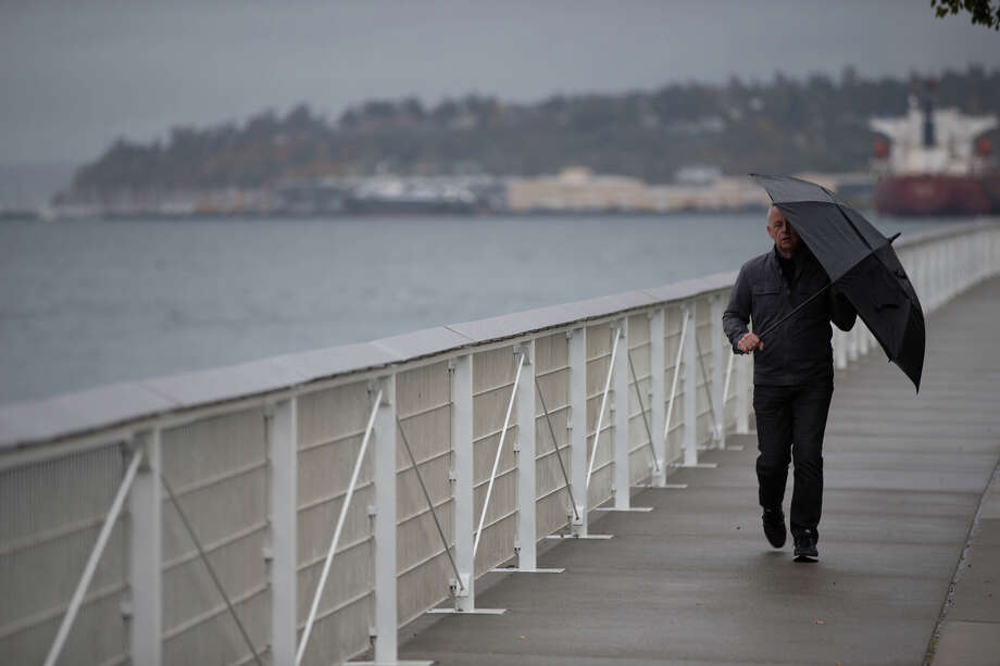 A man shields himself from the rain with an umbrella as he walks along the Elliott Bay Trail on Wednesday, Oct. 18, 2017. Photo: GRANT HINDSLEY, SEATTLEPI.COM / SEATTLEPI.COM