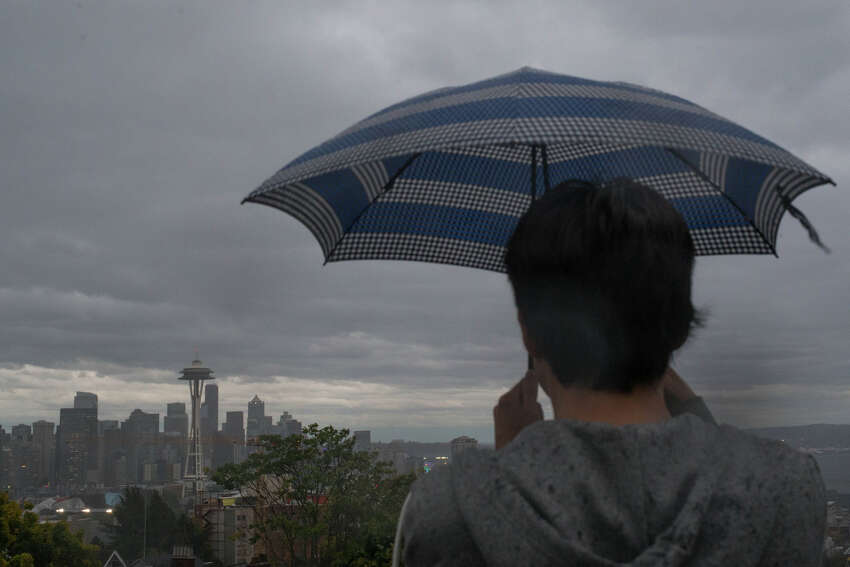 A spectator shields himself from the rain as he takes a photo of the Seattle skyline in the rain on Wednesday, Oct. 18, 2017.