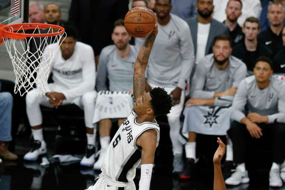Spurs' Dejounte Murray (05) goes in a dunk against Minnesota Timberwolves' Karl-Anthony Towns (32) at the AT&T Center on Wednesday, Oct. 18, 2017.